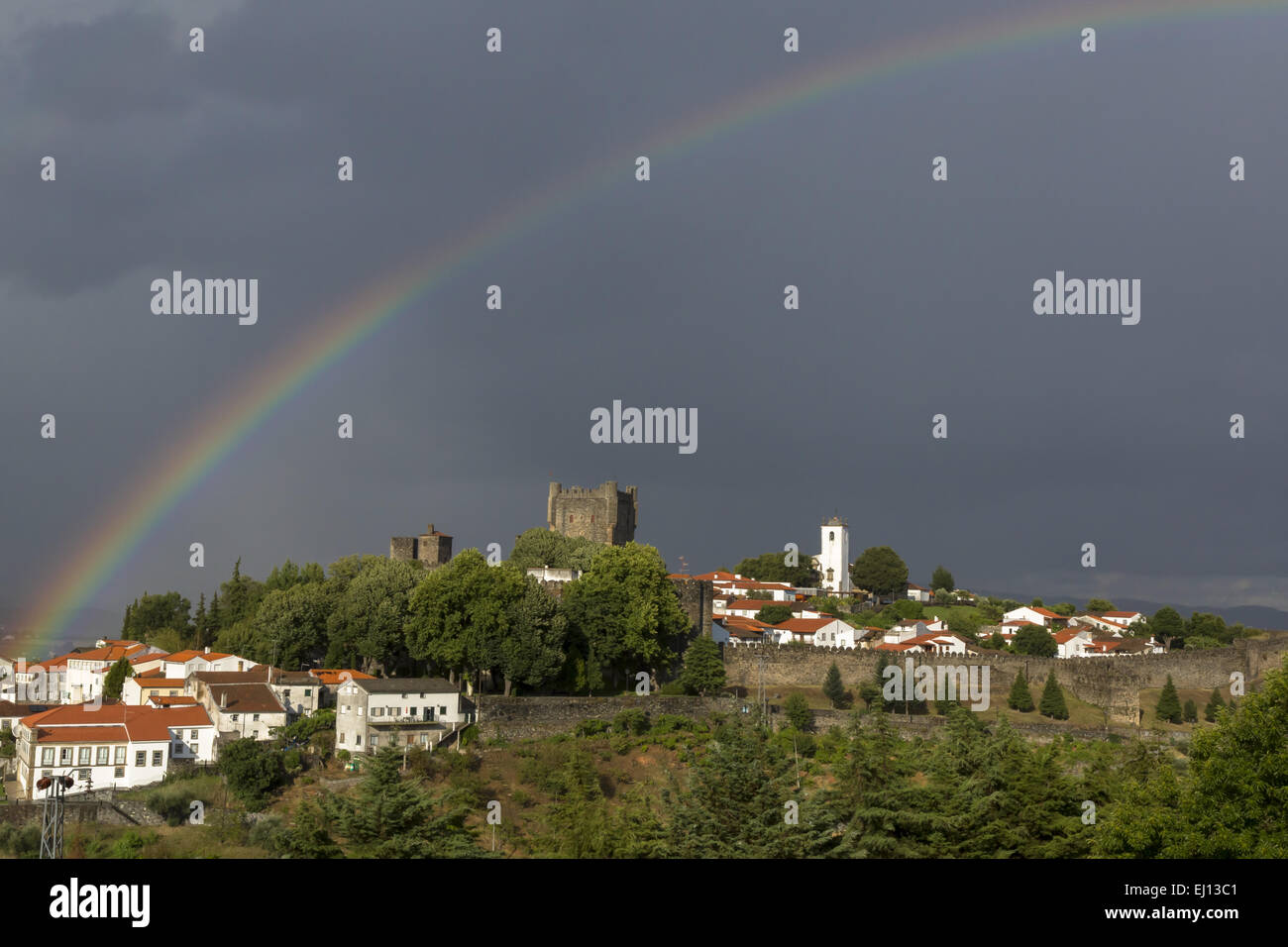 Dramatic view of the ancient walled town of Braganca with dark clouds and rainbow Portugal - Stock Image