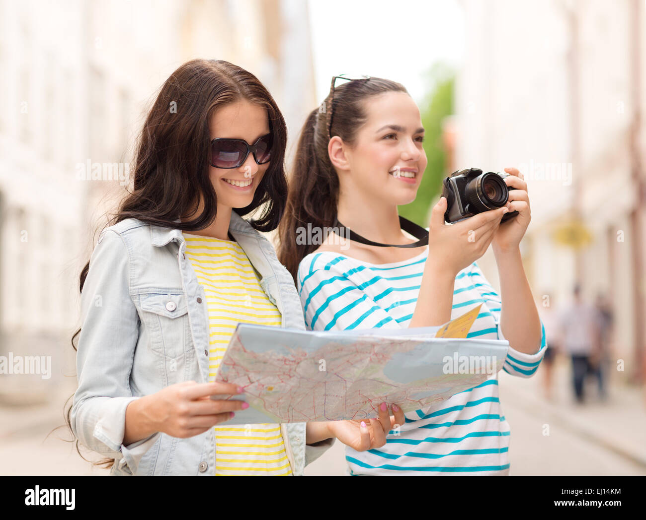 smiling teenage girls with map - Stock Image