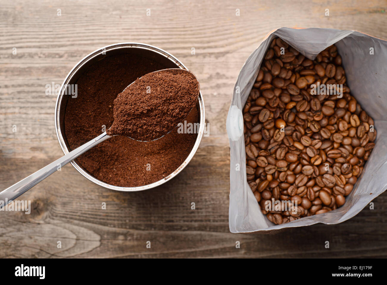 coffee beans and ground coffee on wooden background - Stock Image