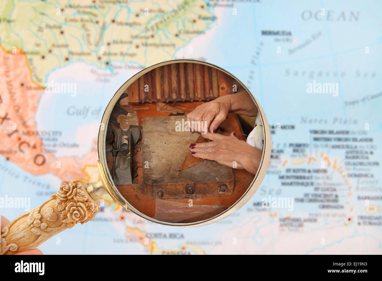 Looking in on a woman making cigars in Cuba with a map of the Caribbean - Stock Image