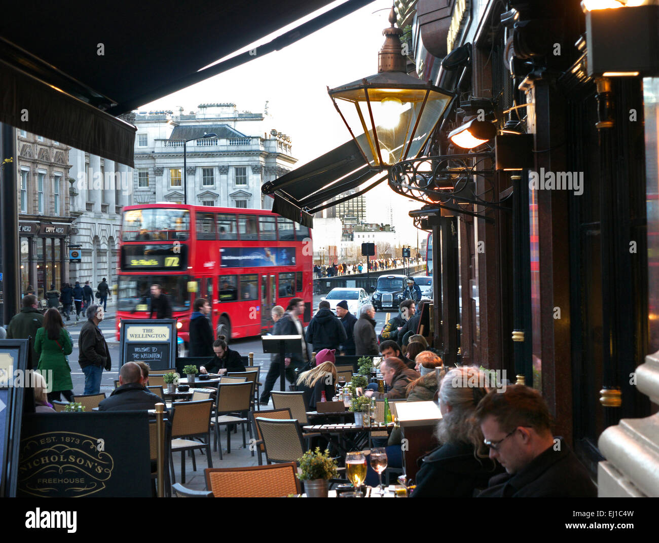 Busy dusk central London scene with red bus taxis commuters and typical real ale pub in foreground The Strand London - Stock Image