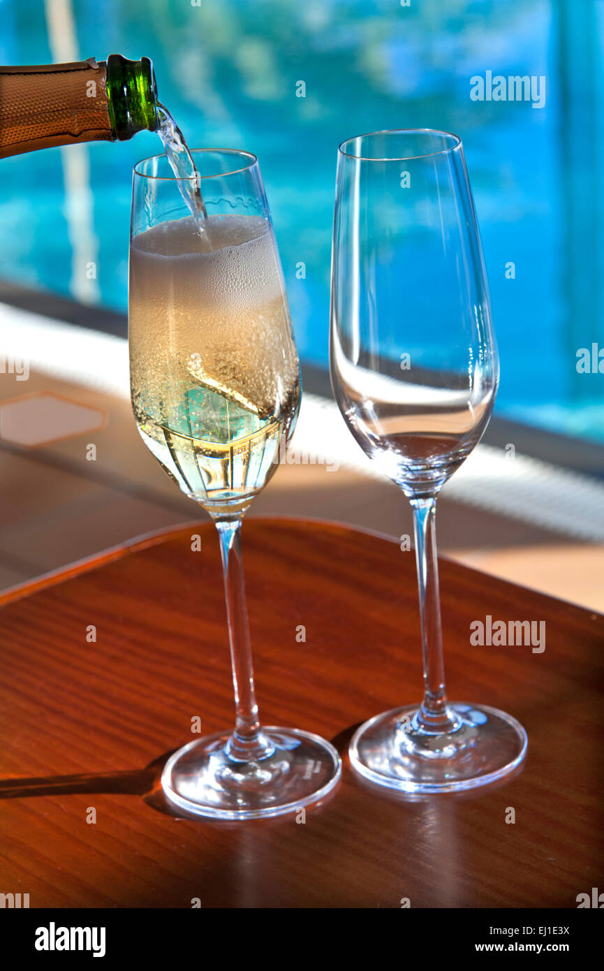 Close view on pouring chilled glass of champagne on sunlit terrace with luxury infinity pool in background - Stock Image
