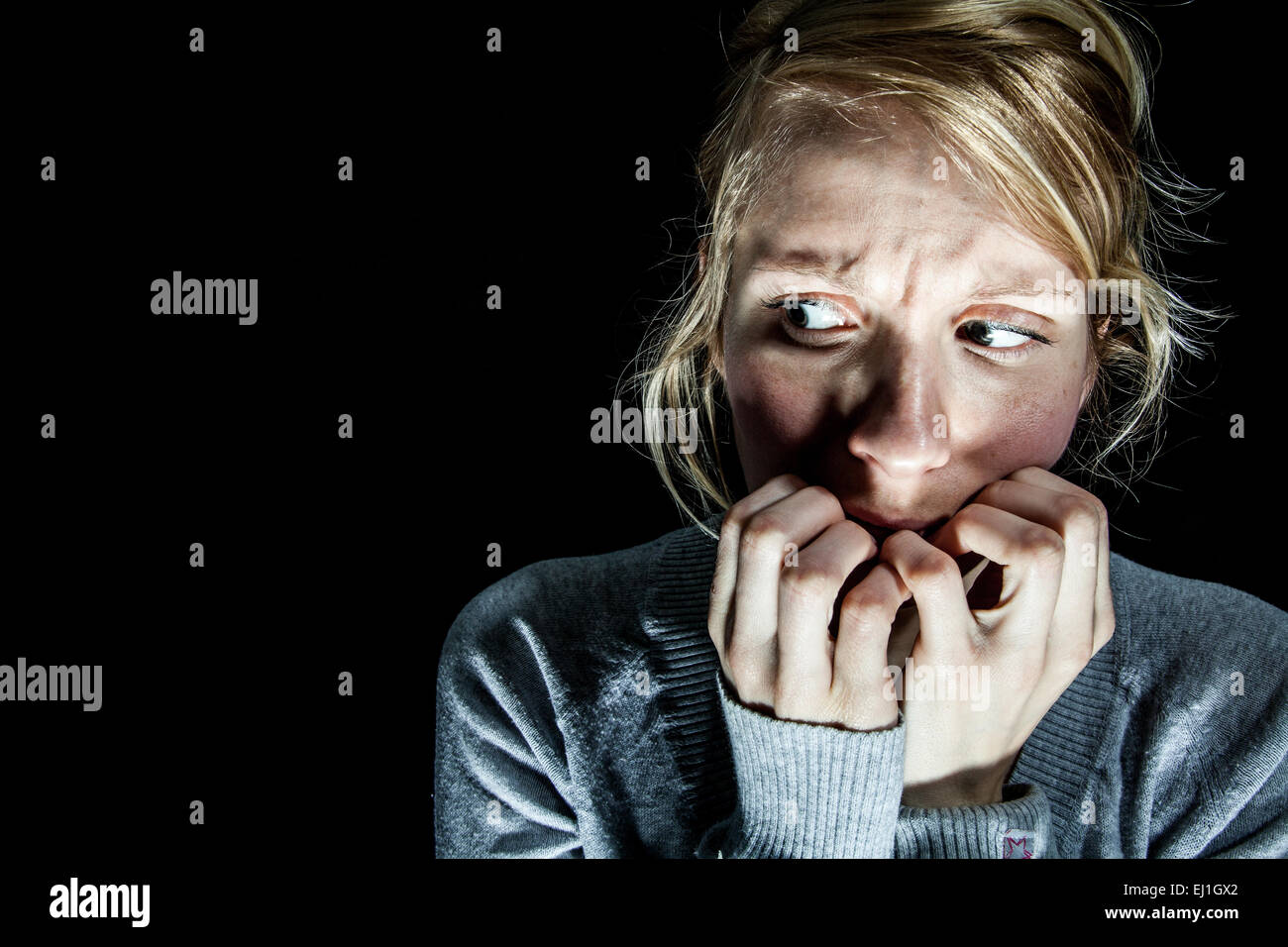 Scary Woman Afraid of something in the Dark - Stock Image