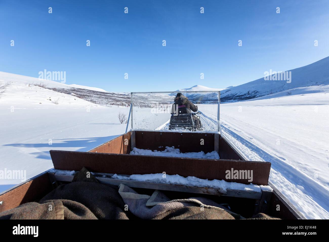 Travelling in the sledge of a snowmobile at Kebnekaise mountain area, Nikkaluokta, Kiruna, Sweden, Europe, EU - Stock Image