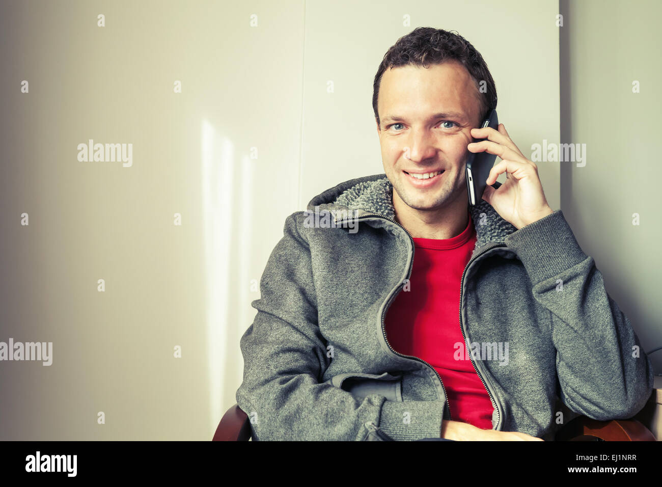 Portrait of sitting young Caucasian man talking on mobile phone. Vintage toned photo with old style filter effect Stock Photo