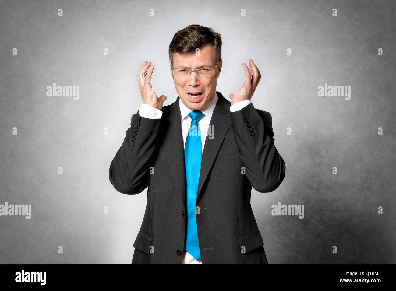 Image of frustrated business man in dark suit - Stock Image