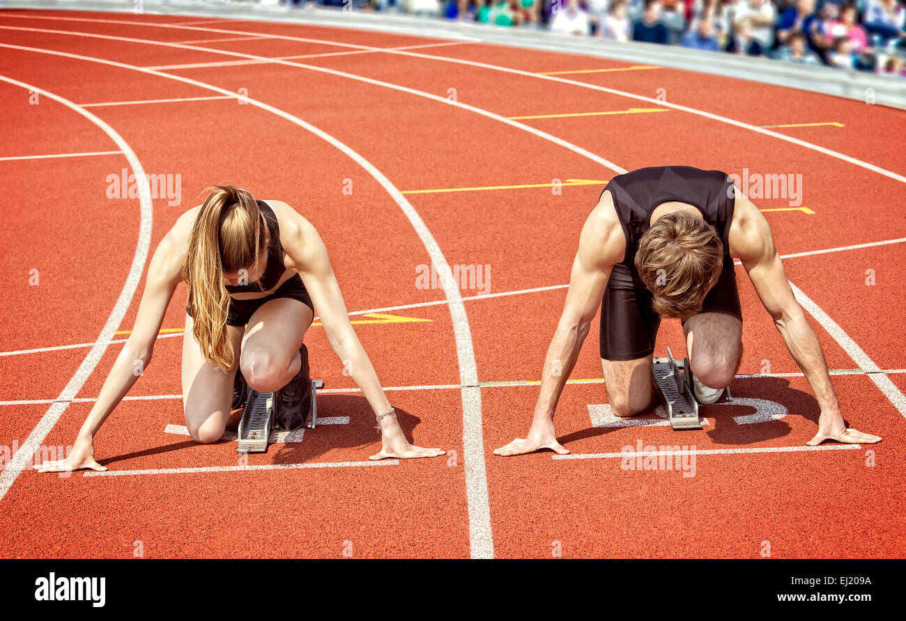 Track and field photo of a sprinter couple kneeling in start position,  ready to start in a curve of a stadium. - Stock Image