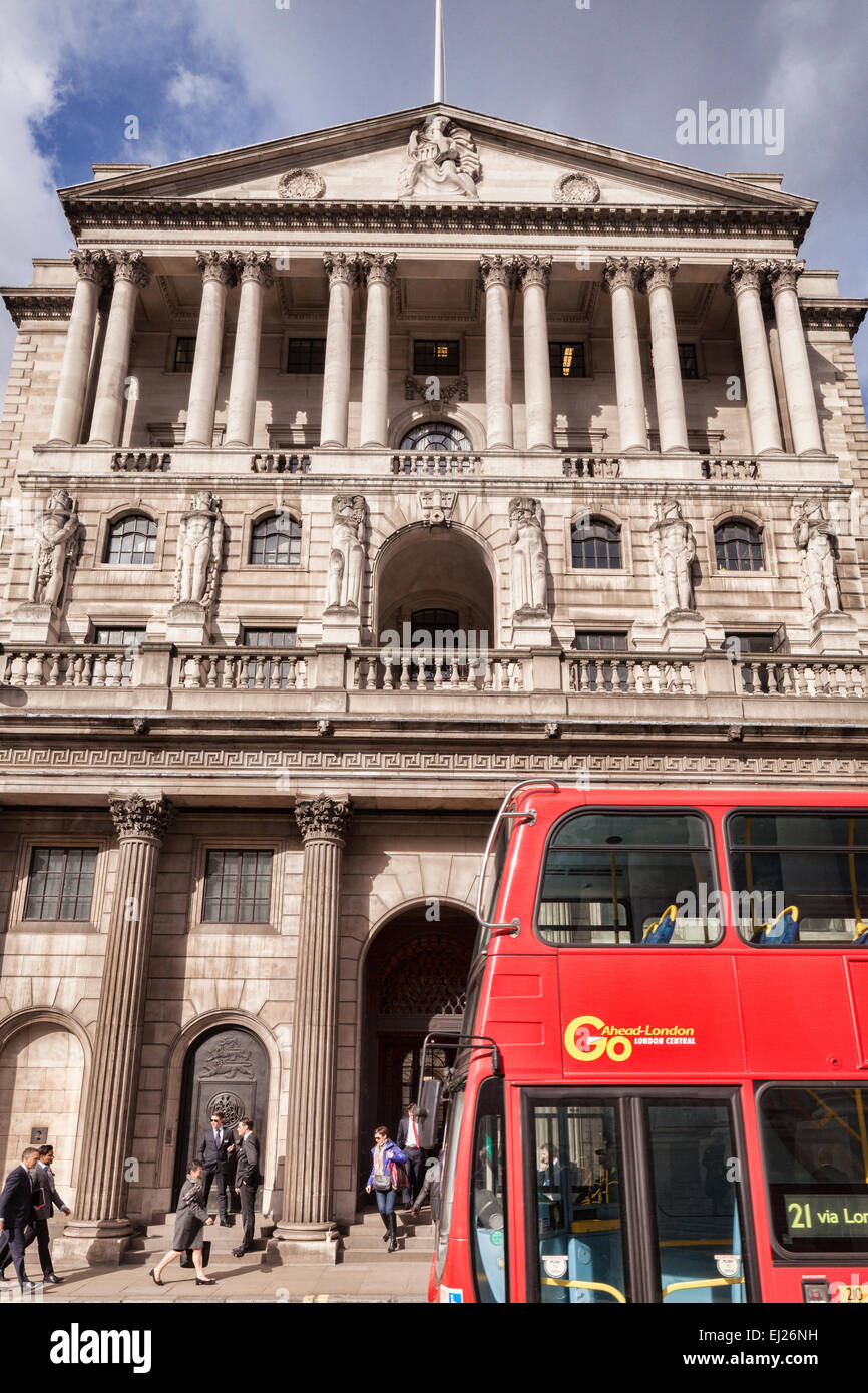 Red double-decker bus passing the Bank of England, Threadneedle Street, London. - Stock Image
