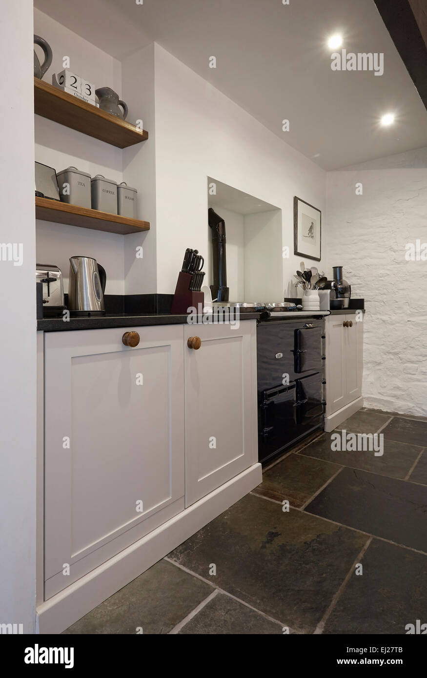 A White country style kitchen in a farmhouse in the UK with stone walls. Stock Photo