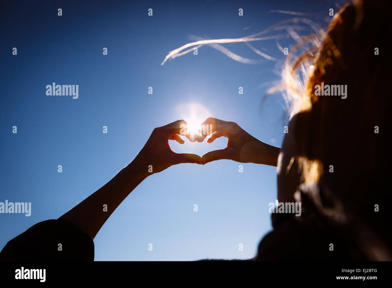 Hands making love shape sign on bright blue sky. - Stock Image