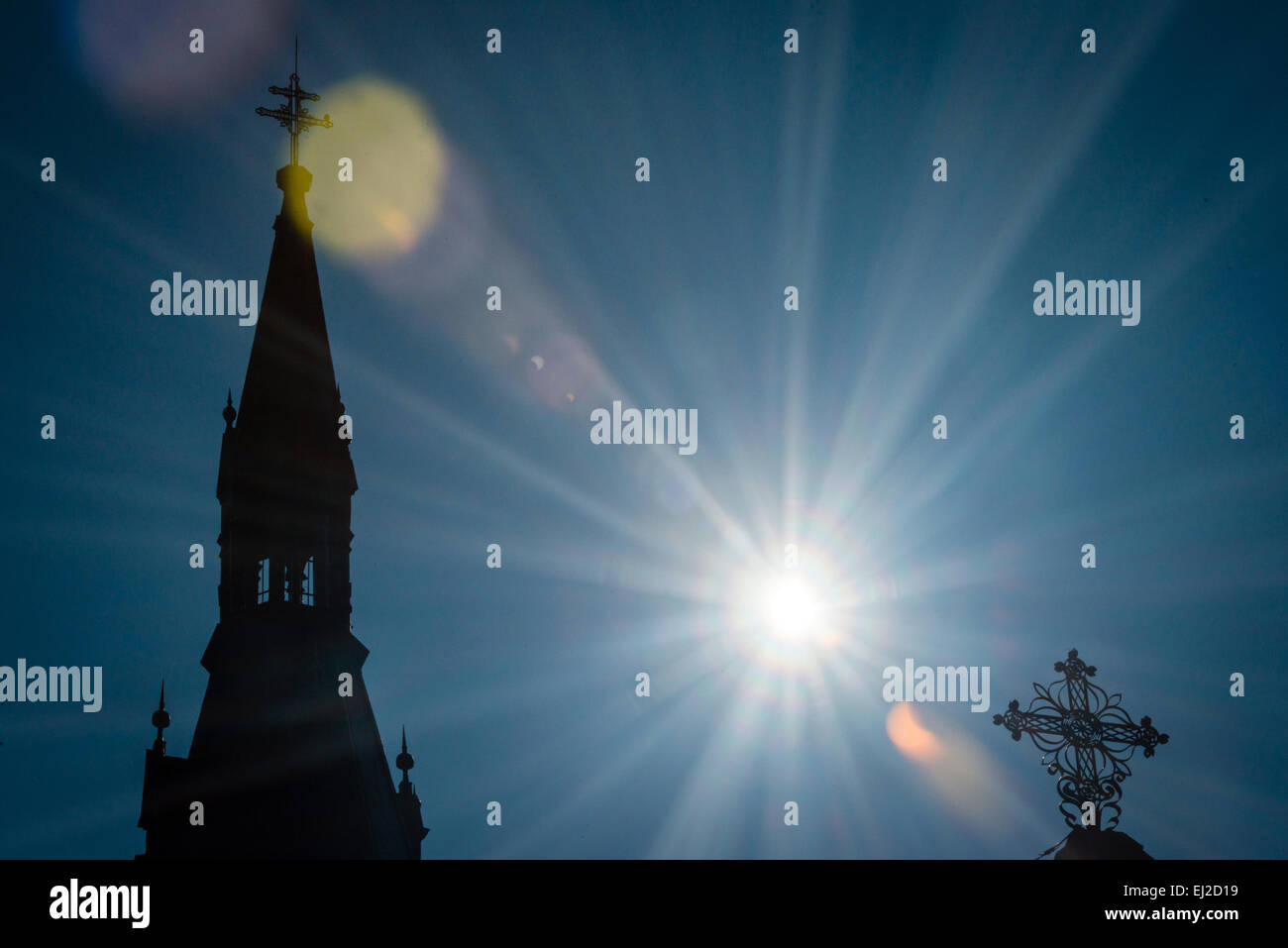 Pezinok, Slovakia. 20th March, 2015. Sickle-shaped sun behind a church during a partial solar eclipse in Pezinok, - Stock Image