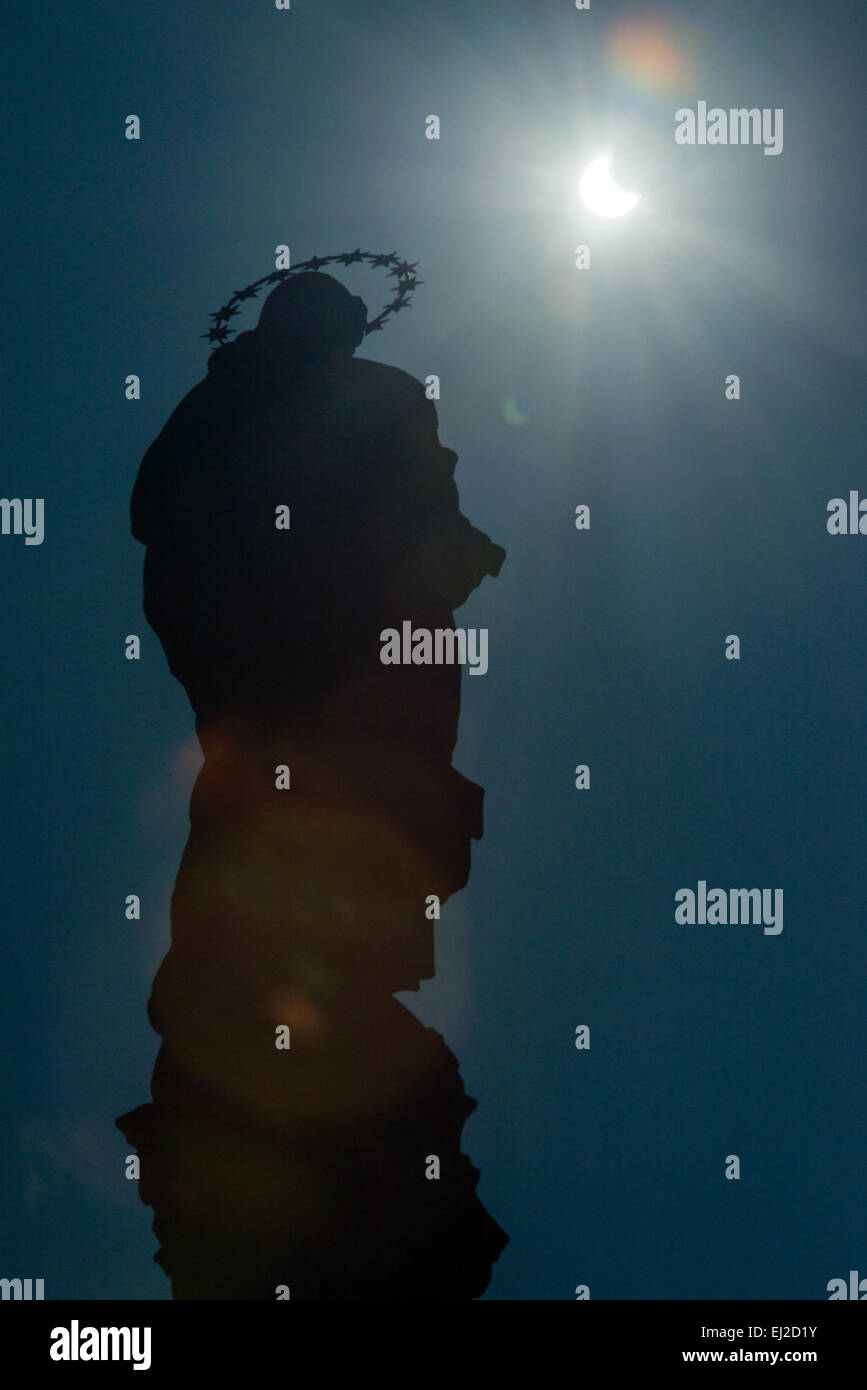 Pezinok, Slovakia. 20th March, 2015. Sickle-shaped sun behind a statue during a partial solar eclipse in Pezinok, - Stock Image