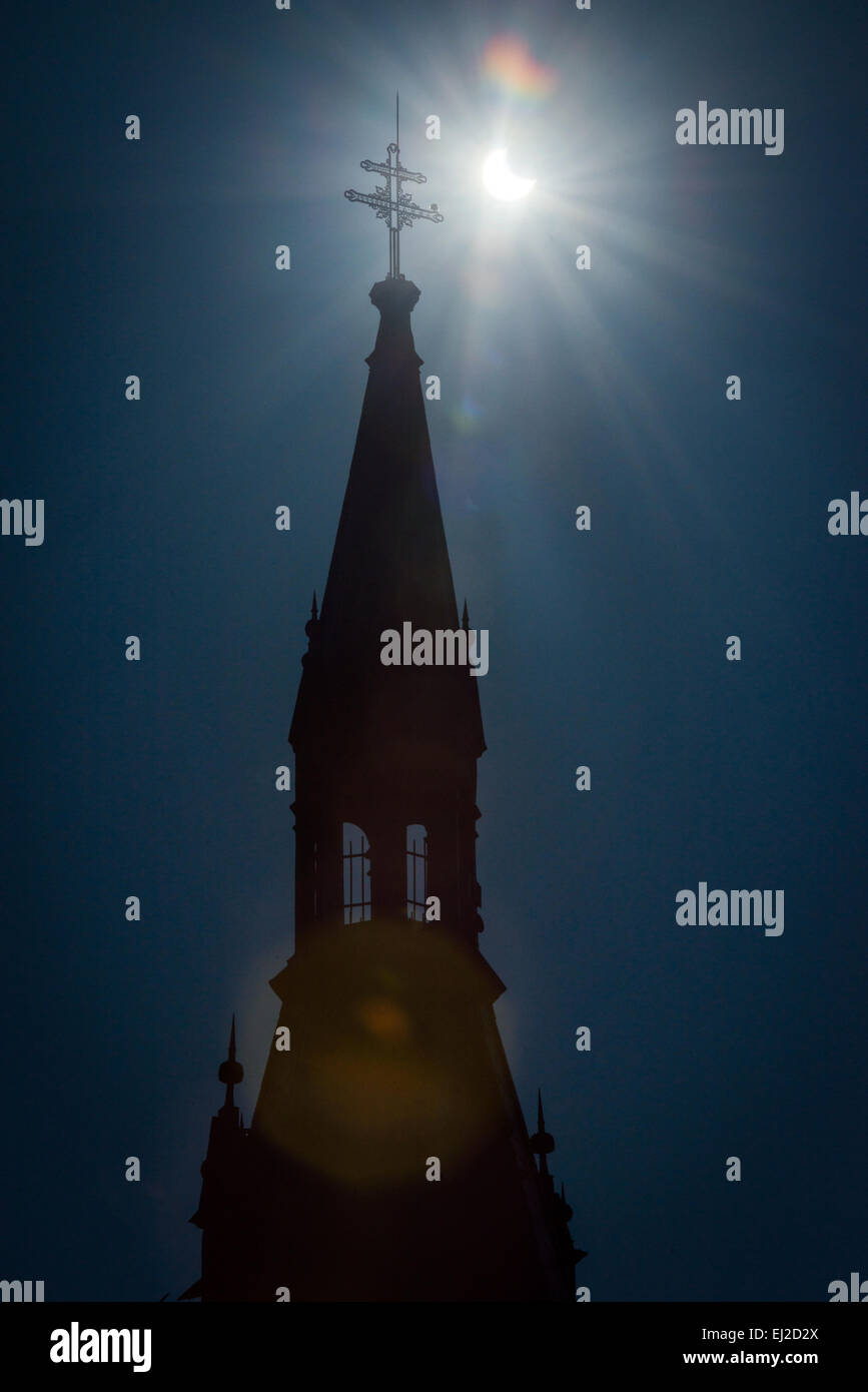 Pezinok, Slovakia. 20th March, 2015. Sickle-shaped sun behind a church roof during a partial solar eclipse in Pezinok, - Stock Image