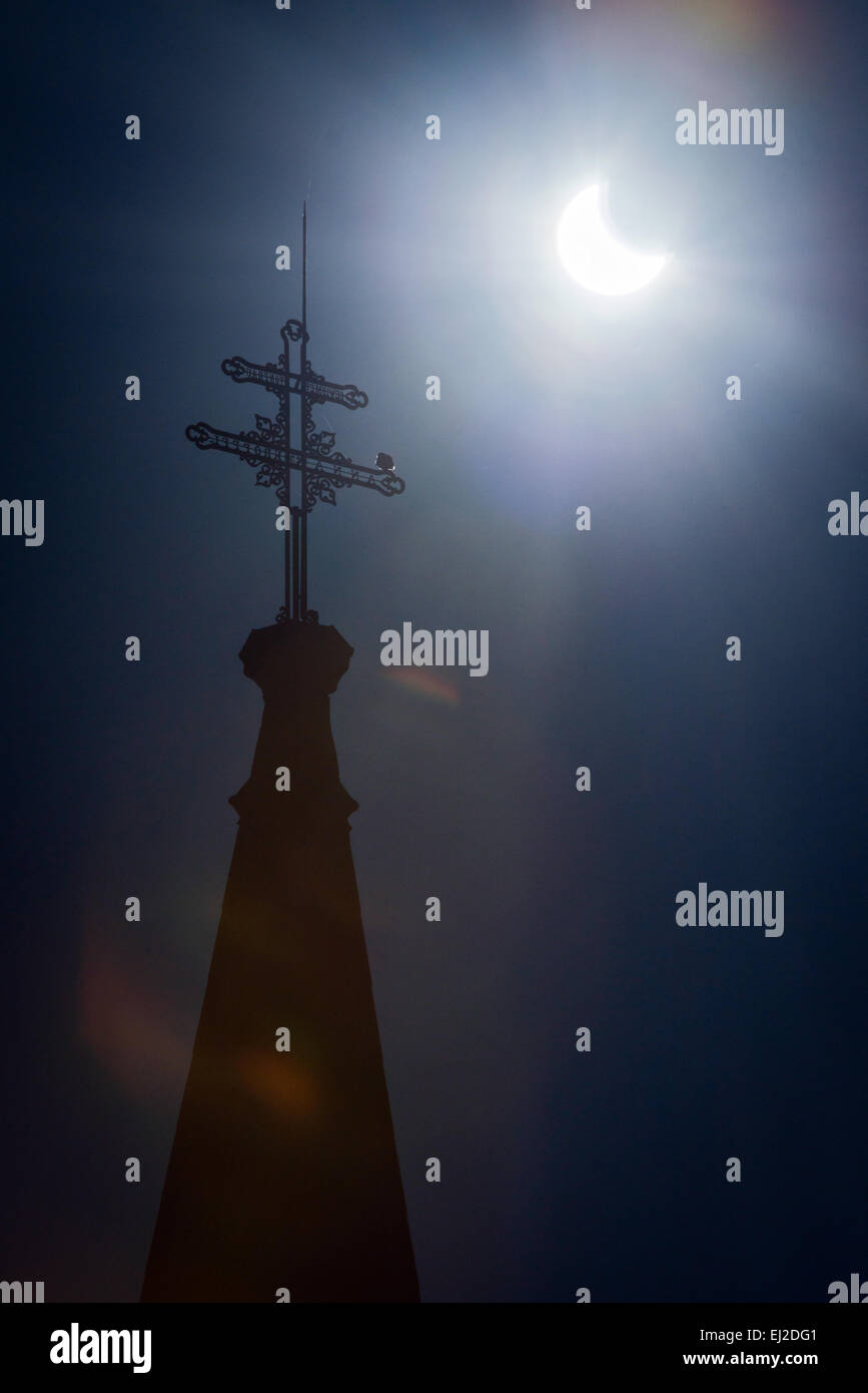 Pezinok, Slovakia. 20th March, 2015.Sickle-shaped sun behind a church roof during a partial solar eclipse in Pezinok, - Stock Image