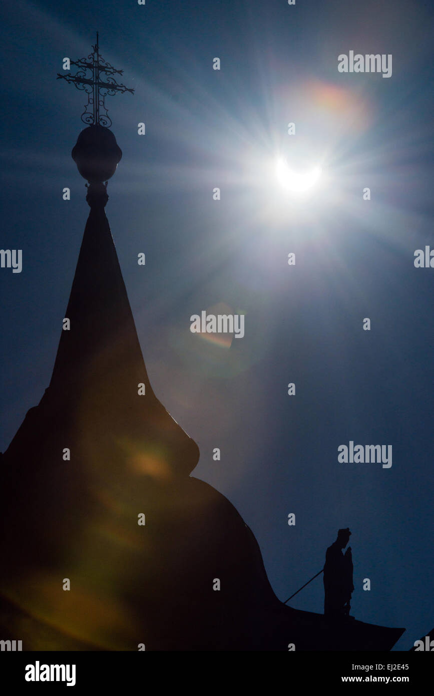 Svaty Jur, Slovakia. 20th March, 2015. Sickle-shaped sun with a  church roof and statue during partial solar eclipse - Stock Image