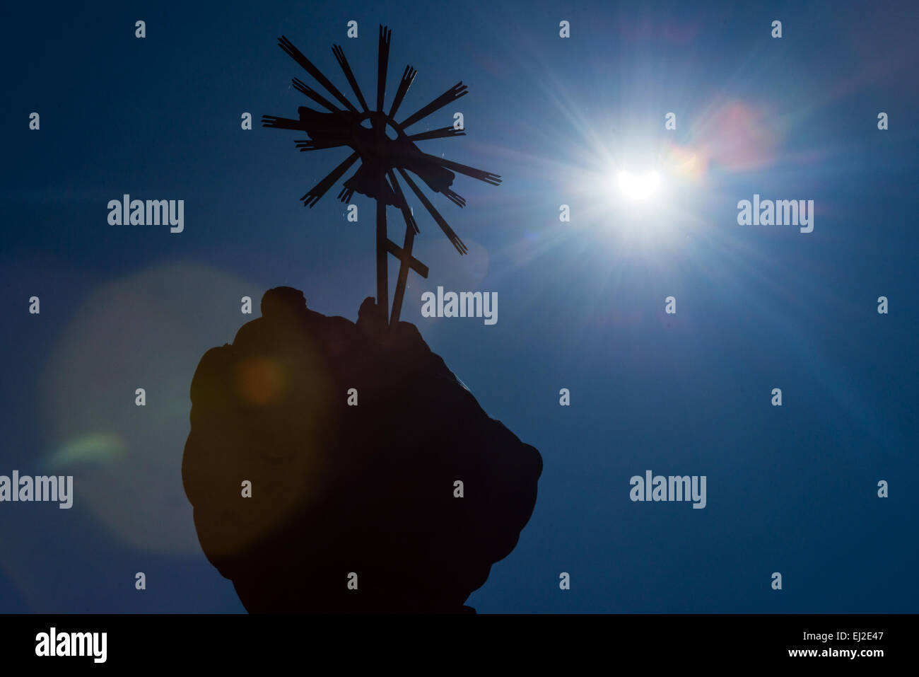 Svaty Jur, Slovakia. 20th March, 2015. Sickle-shaped sun with a  statue during partial solar eclipse in Svaty Jur, - Stock Image