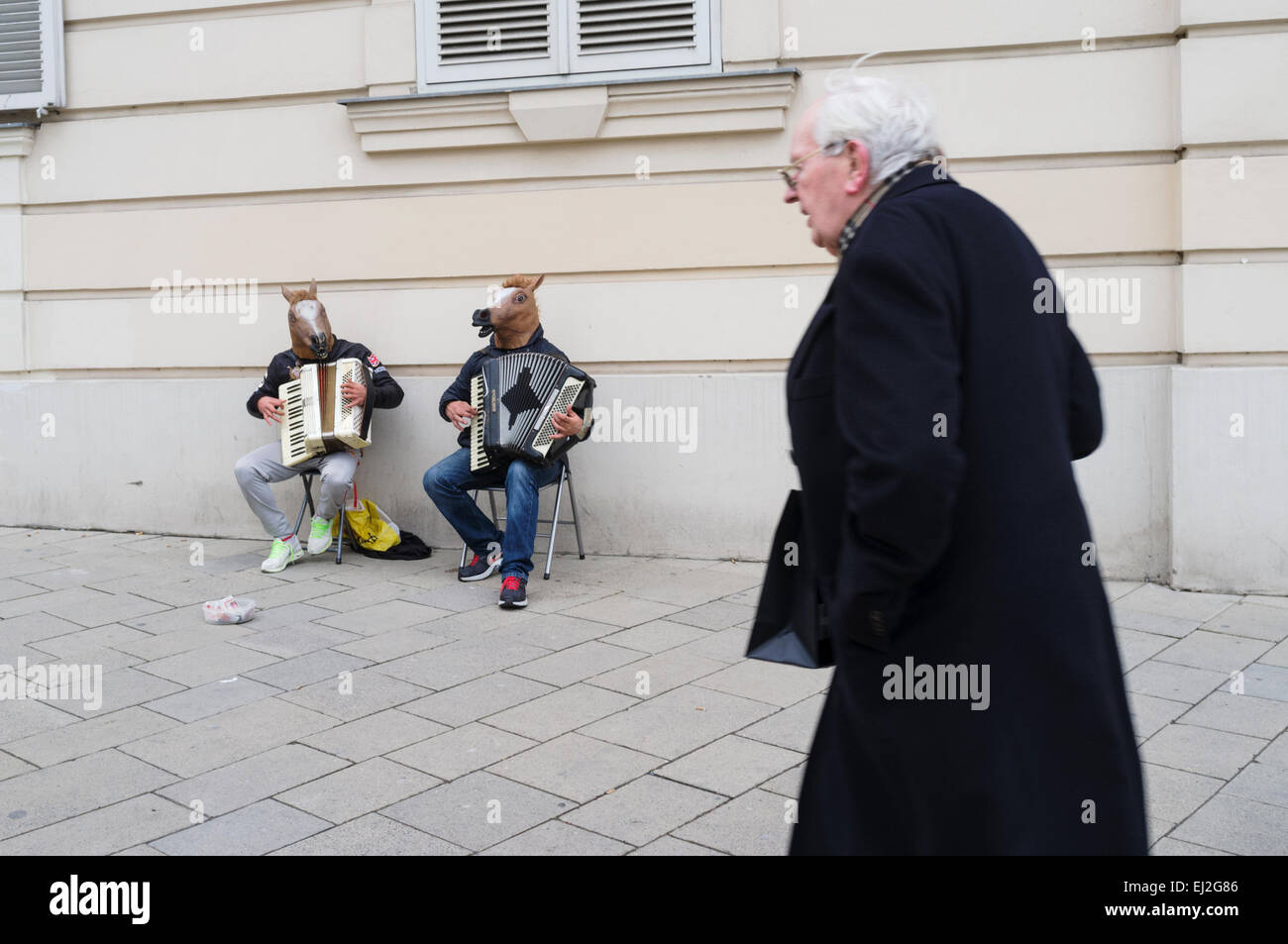 Buskers with horse heads playing accordion. Vienna, Austria - Stock Image