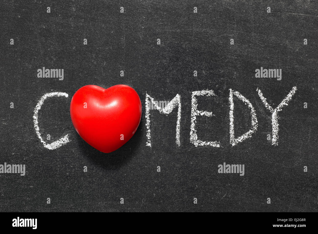 comedy word handwritten on blackboard with heart symbol instead of O - Stock Image