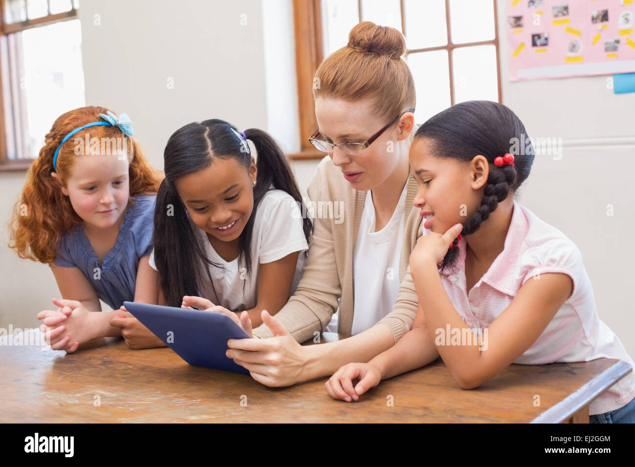 Teacher and pupils looking at tablet computer - Stock Image