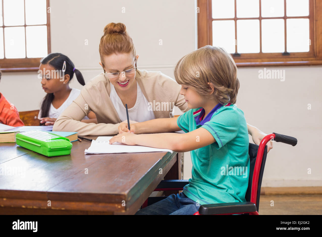 Pretty teacher helping pupil in classroom - Stock Image