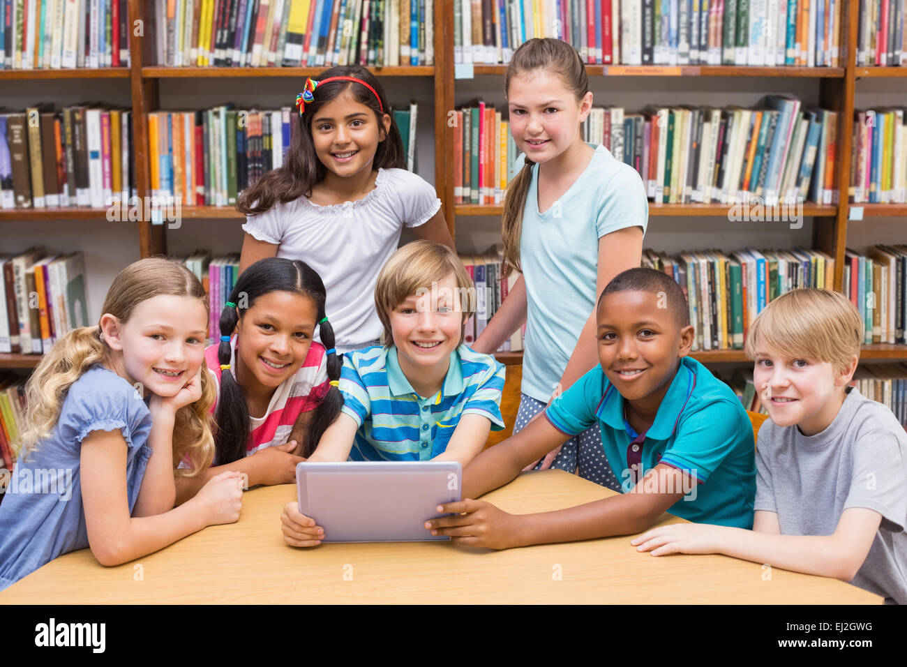 Cute pupils using tablet computer in library - Stock Image