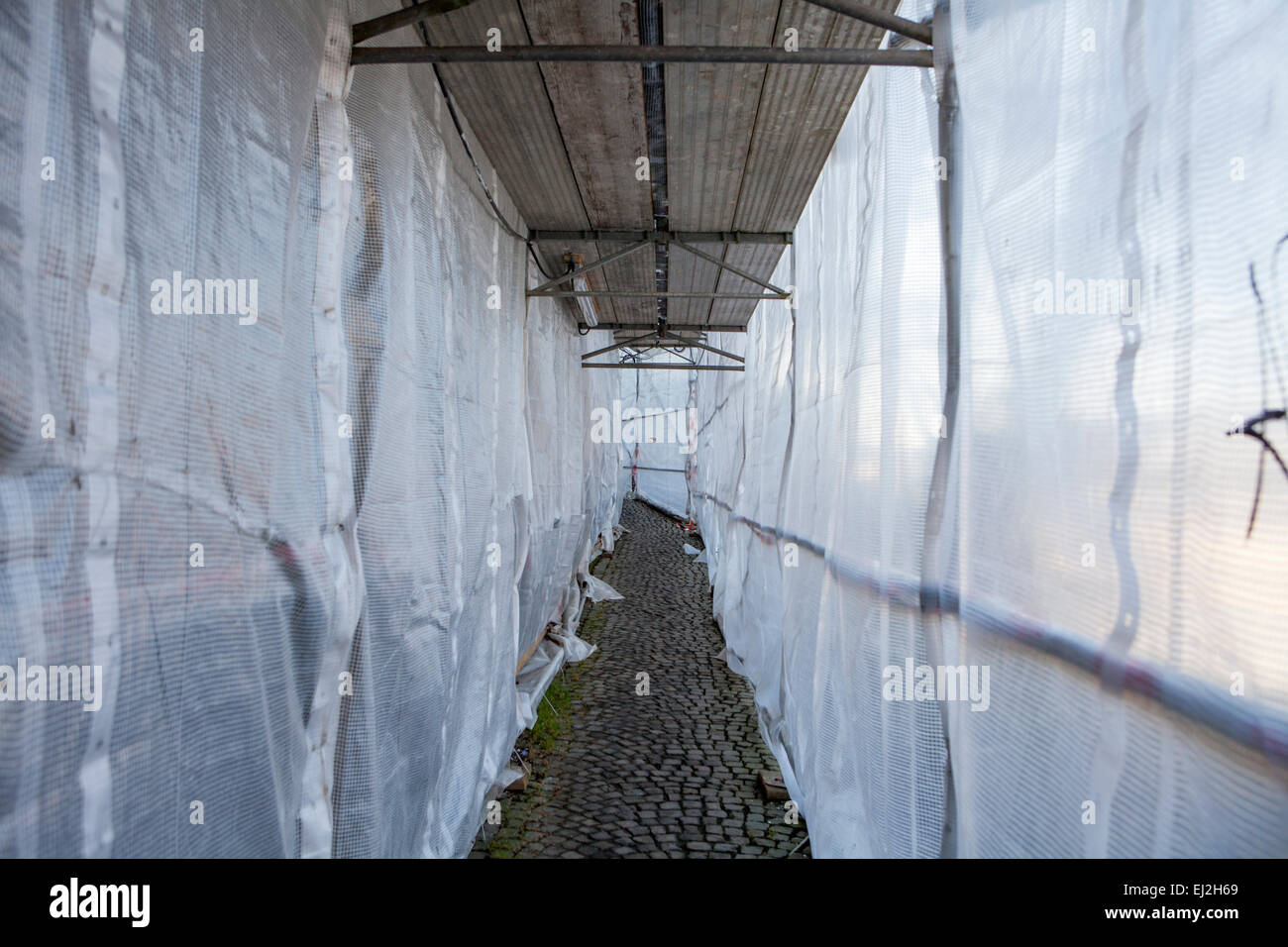Footpath through a scaffolding with tarpaulin - Stock Image