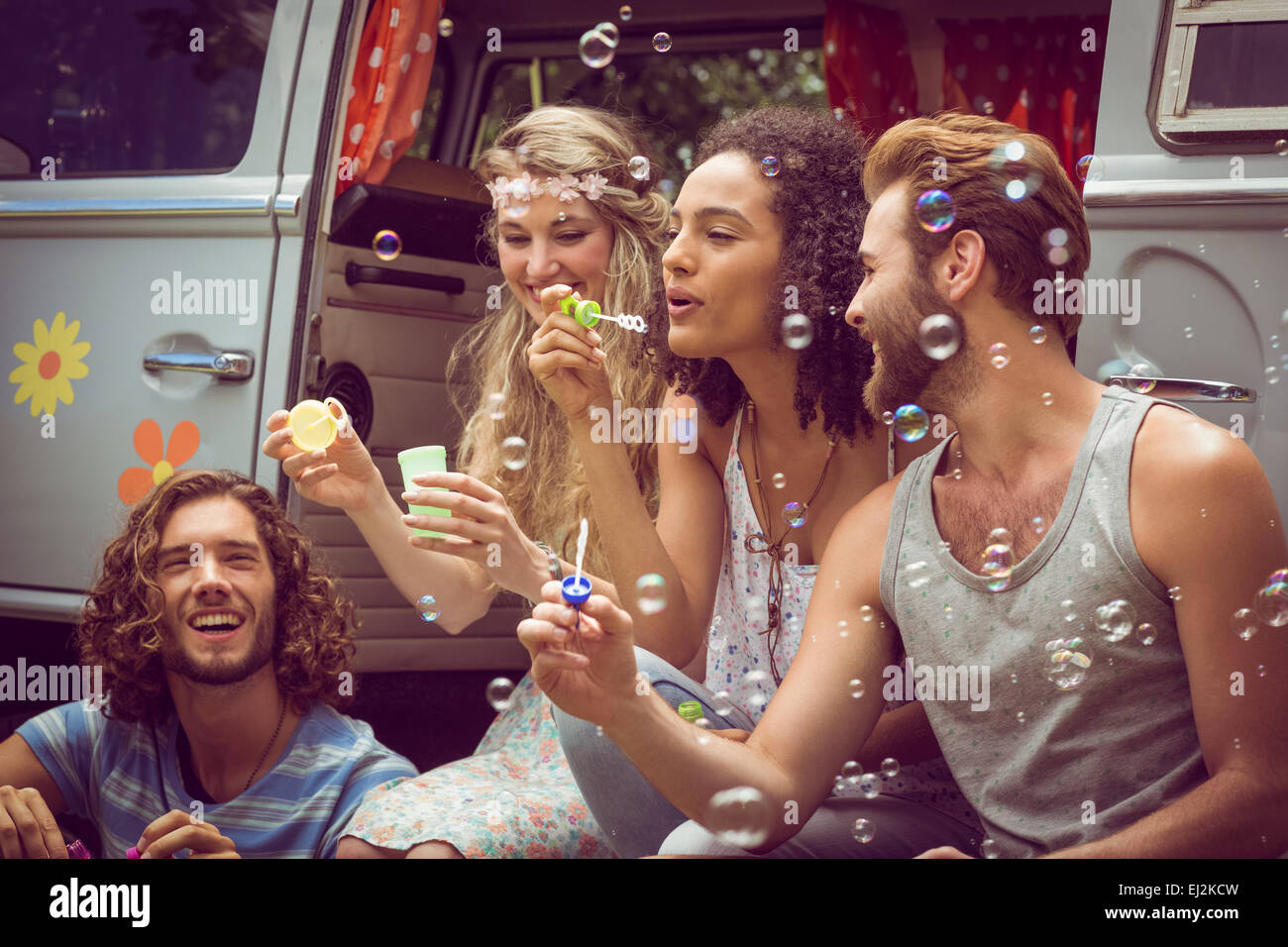 Hipsters blowing bubbles in camper van - Stock Image