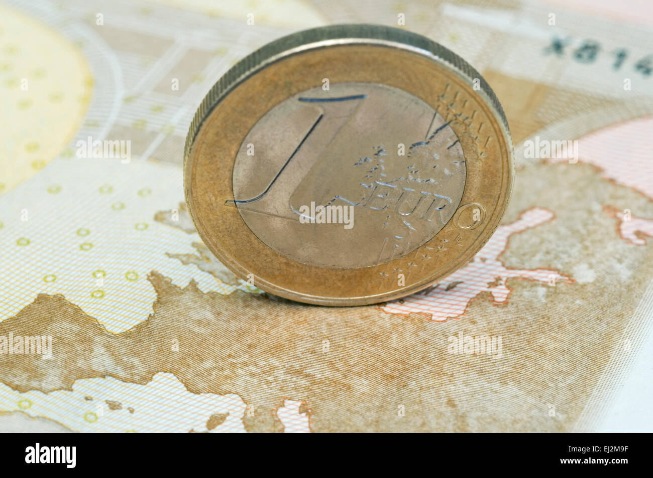one euro coin standing on the map of a banknote - Stock Image