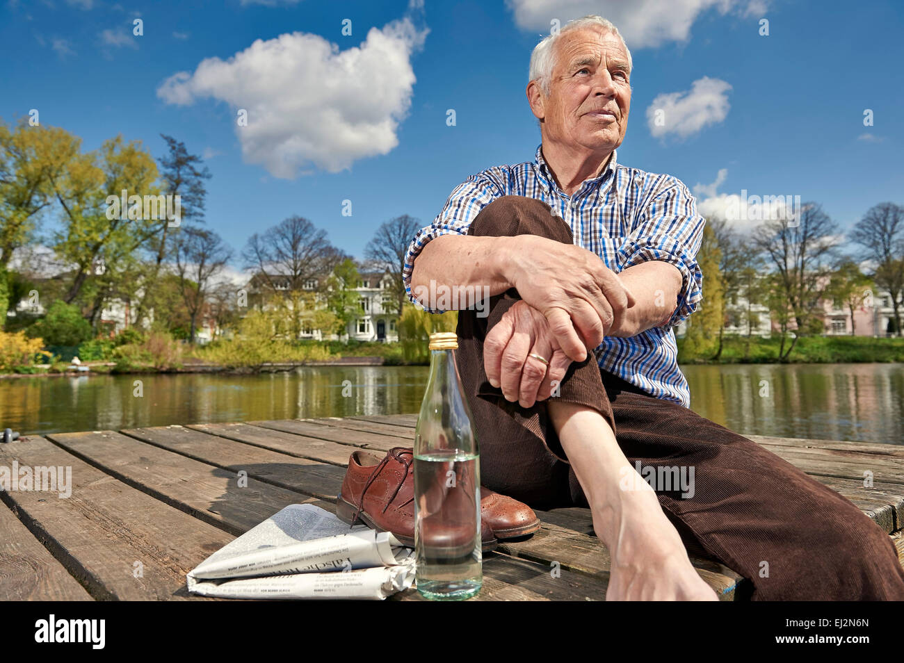 Senior sitting on a boardwalk in summer - Stock Image