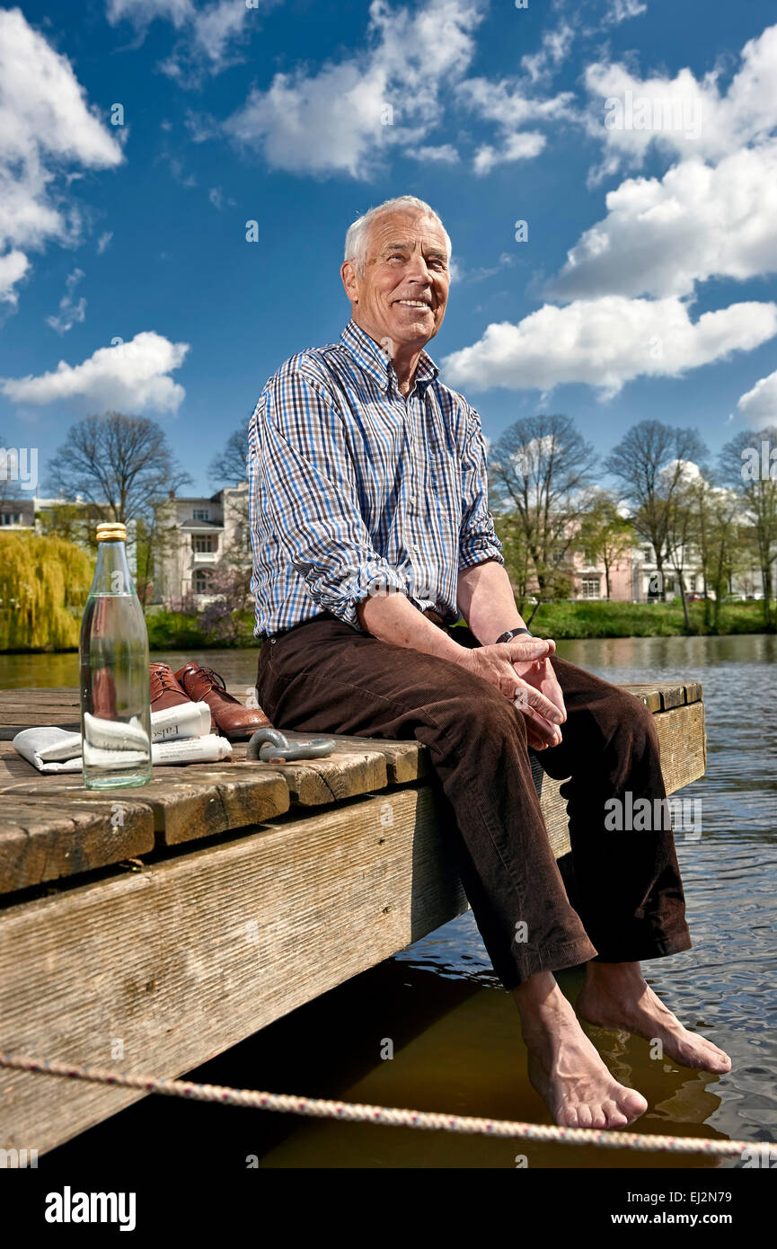 Senior sitting barefoot on a boardwalk in summer - Stock Image