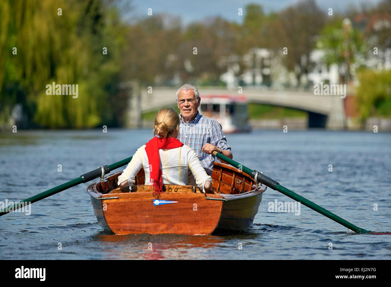 Senior and his daughter riding a rowboat - Stock Image