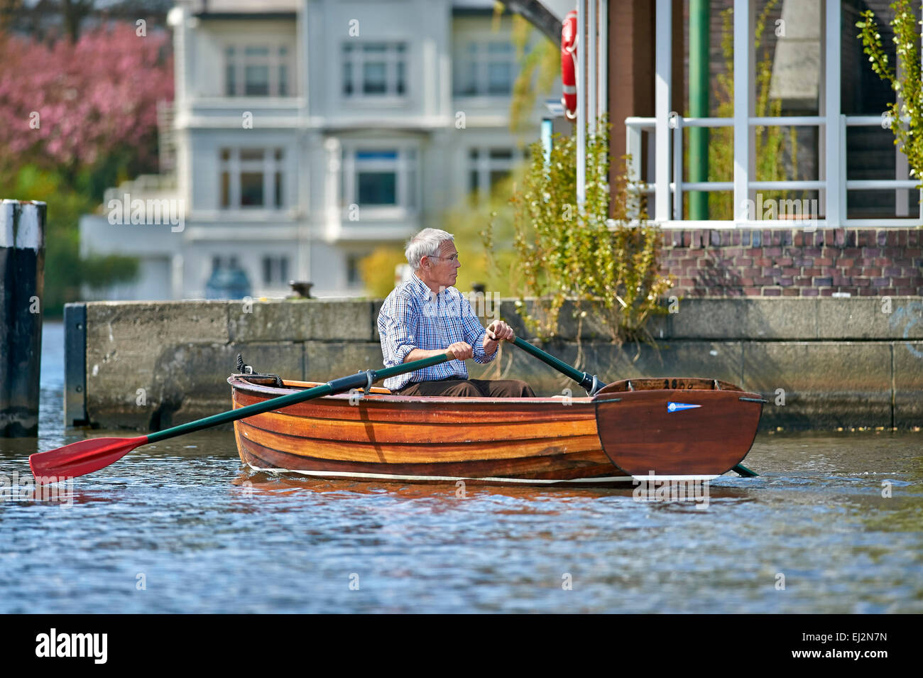 Senior riding a rowboat on the Alster in Hamburg - Stock Image