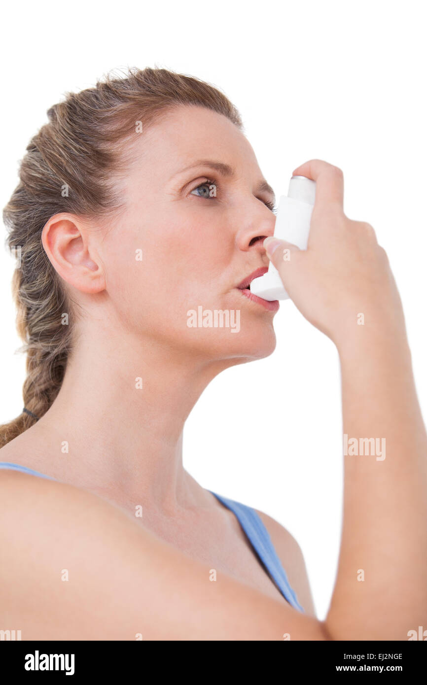 Woman using inhaler for asthma - Stock Image