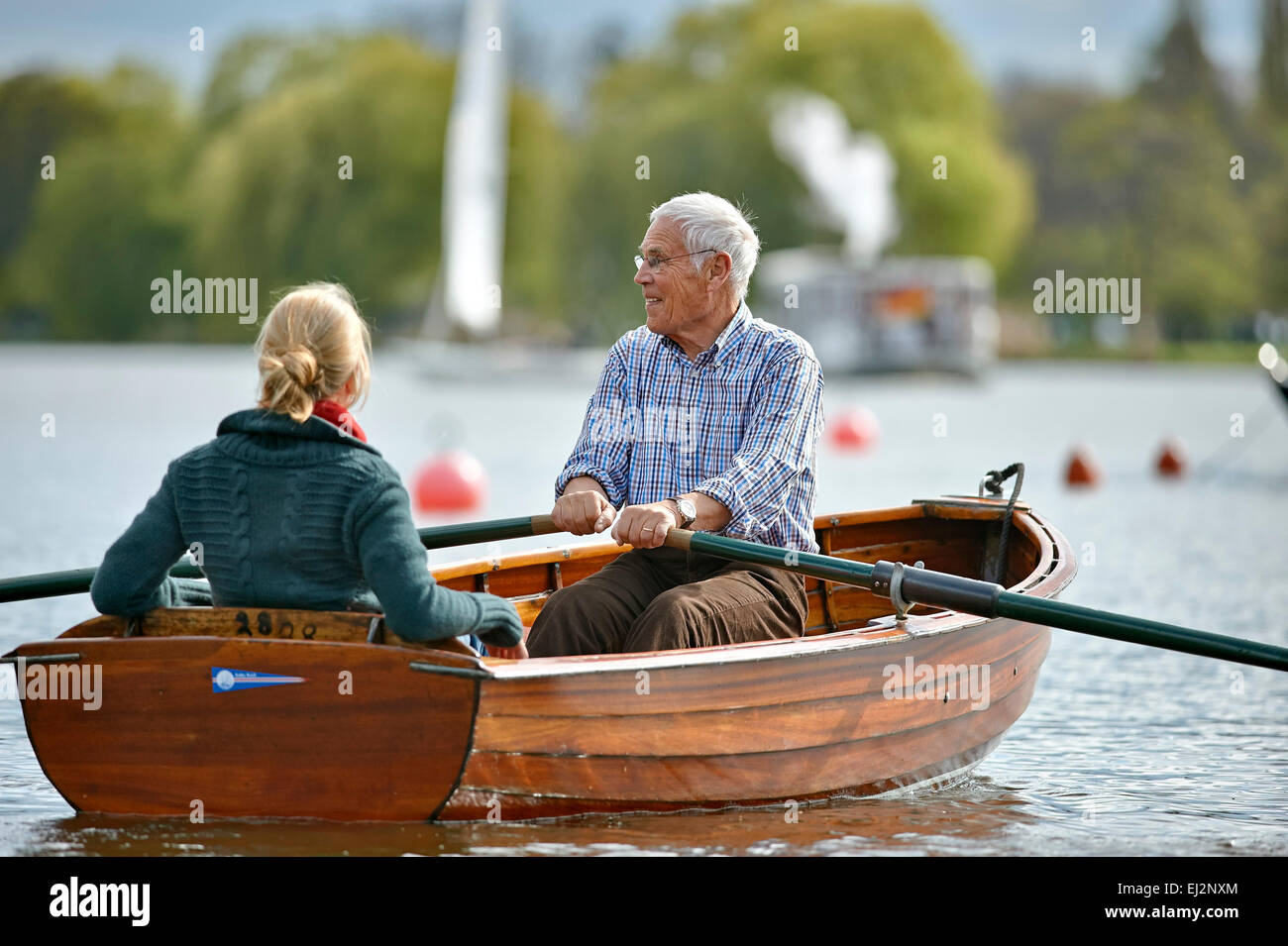 Senior and his daughter riding on a rowboat - Stock Image