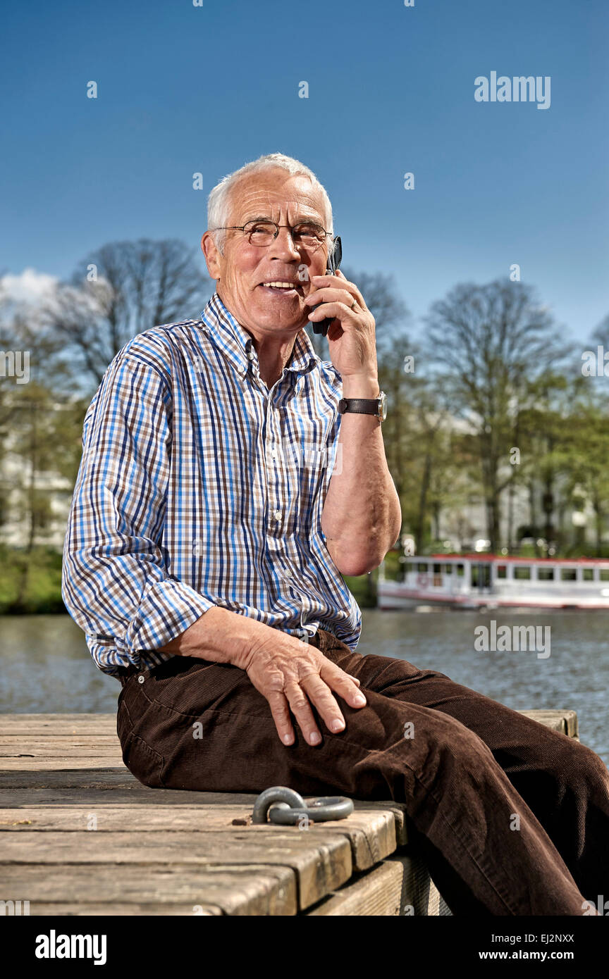 Senior sitting on a boardwalk with his mobile - Stock Image