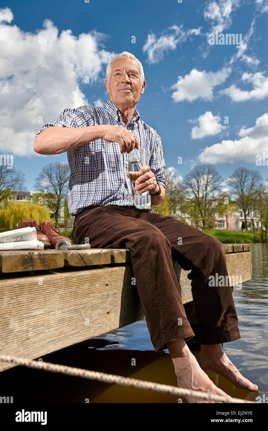 Senior sitting on a boardwalk and drinking water - Stock Image