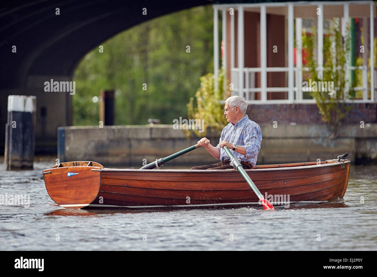 Senior riding on a rowboat on the Alster in Hamburg - Stock Image
