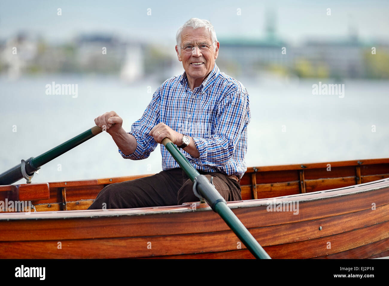 Senior riding on a rowboat - Stock Image