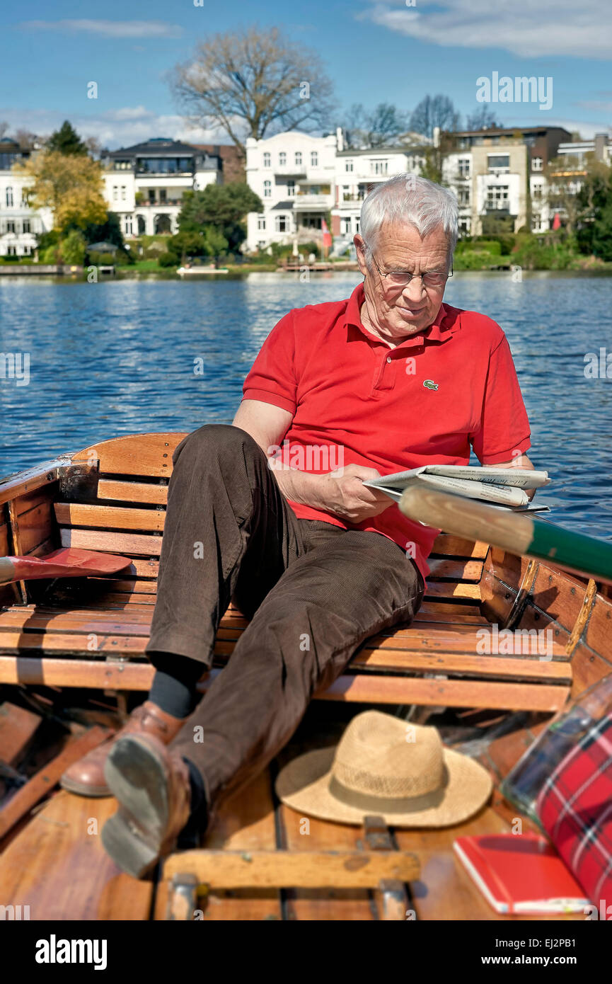 Senior is reading a newspaper on a rowboat - Stock Image