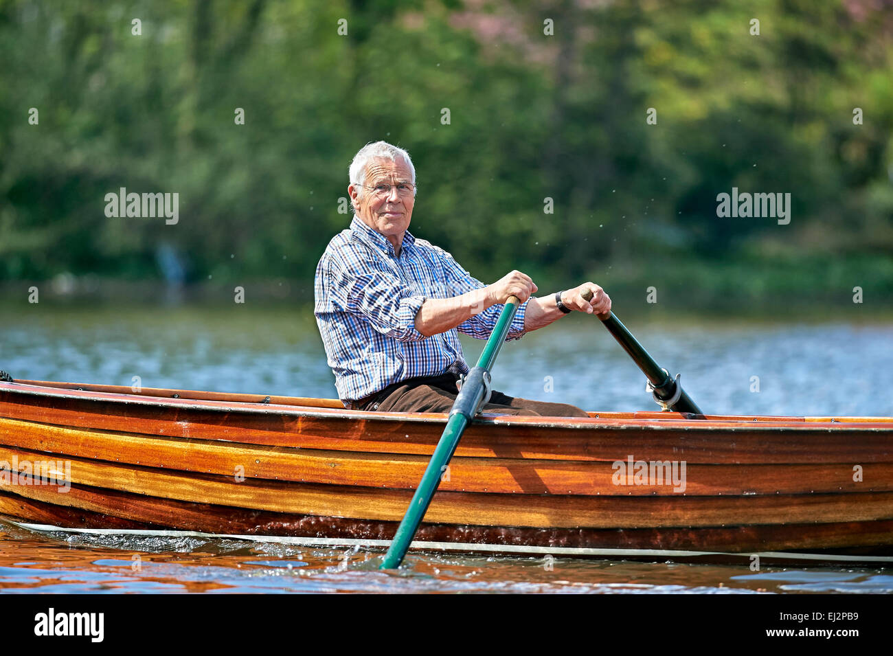 Senior riding a rowboat - Stock Image