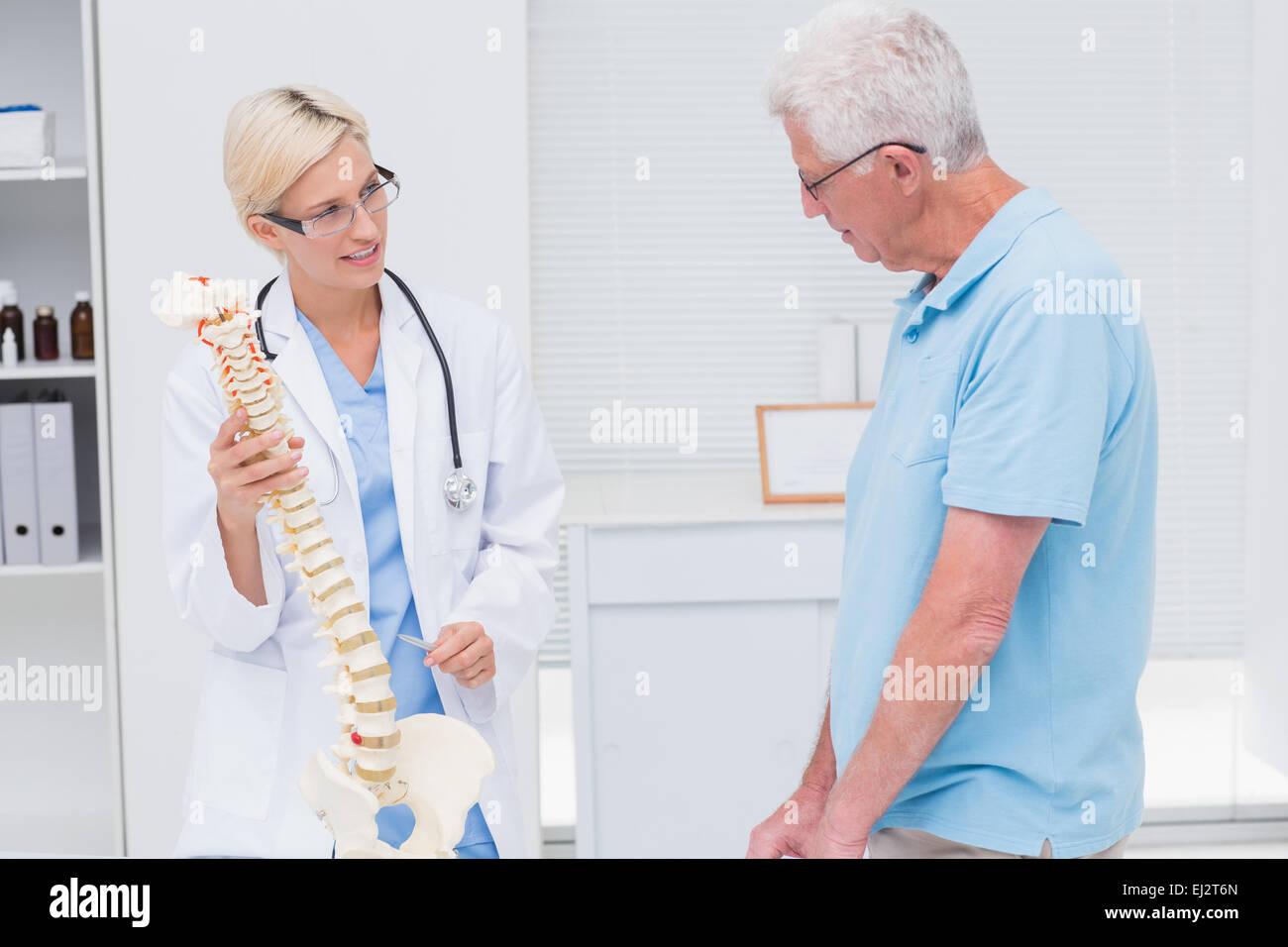 Orthopedic Doctor Explaining Anatomical Spine To Senior Man