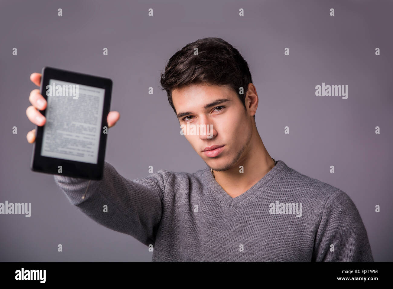 Handsome young man holding and showing ebook reader and looking at camera, sitting on grey background - Stock Image