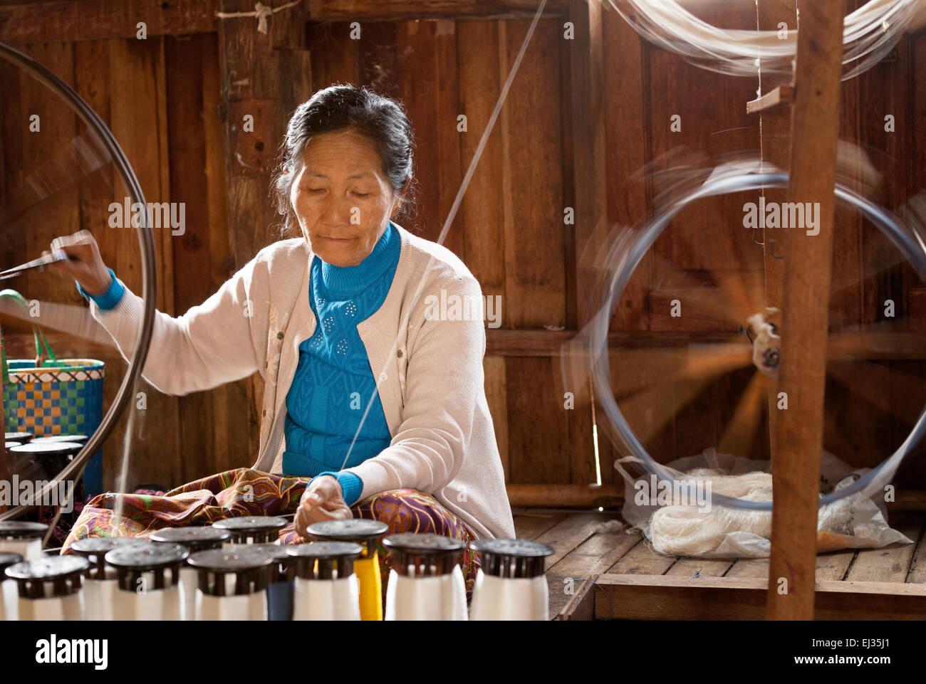 Senior burmese woman spinning silk yarn on a spinning wheel, In Paw Khone village, Inle Lake, Myanmar ( Burma ), Stock Photo
