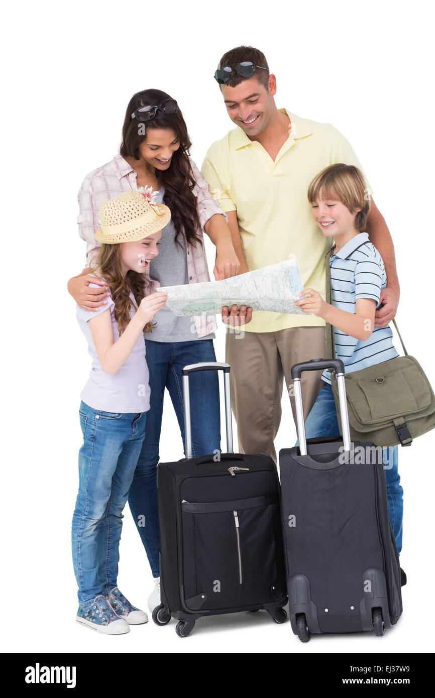 Family with luggage exploring map - Stock Image
