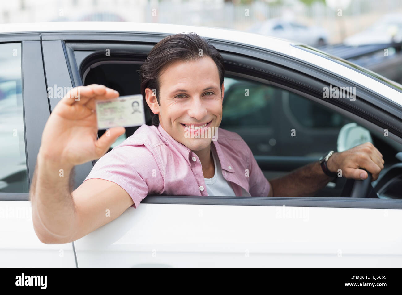 Man smiling and holding his driving license Stock Photo