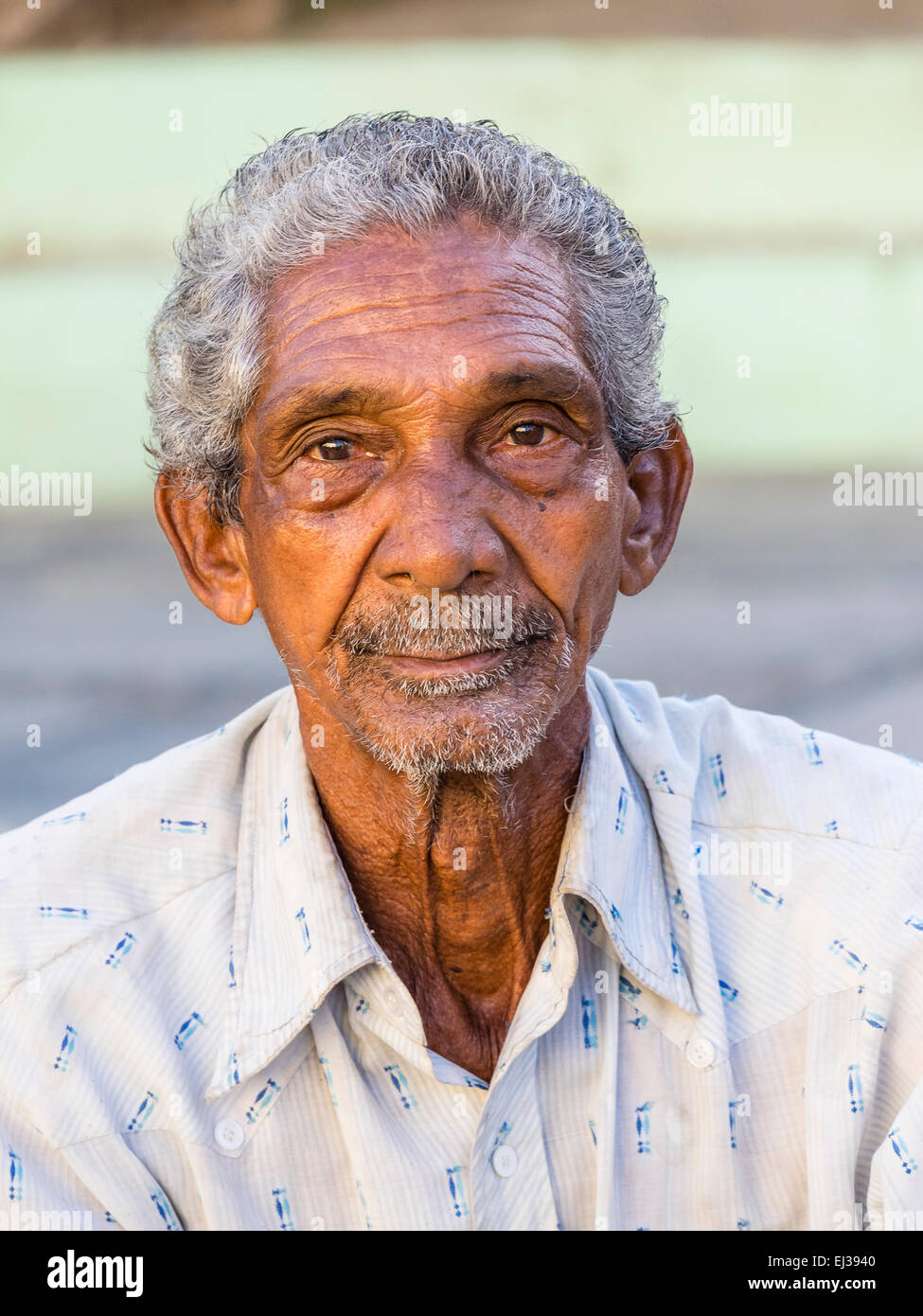 A head and shoulders close-up of Afro-Cuban male senior citizen not smiling. - Stock Image