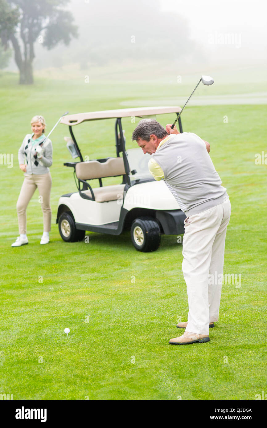 Golfer about to tee off with partner behind him - Stock Image