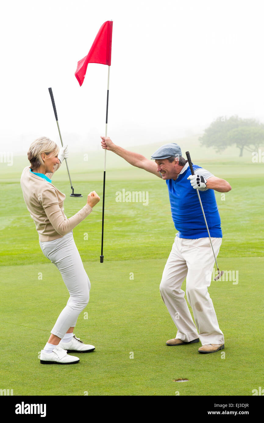 Cheering golfing couple - Stock Image