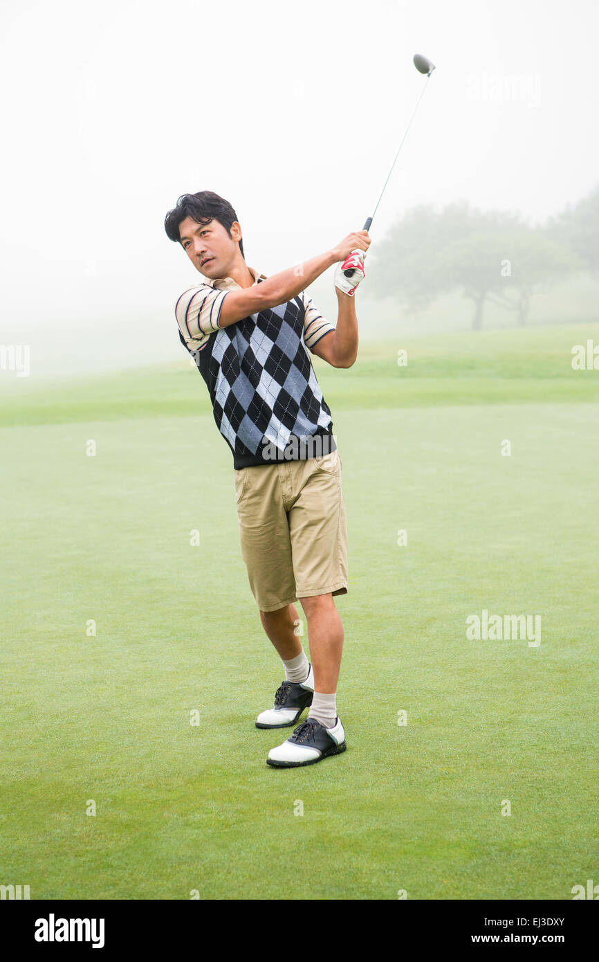 Golfer teeing off - Stock Image