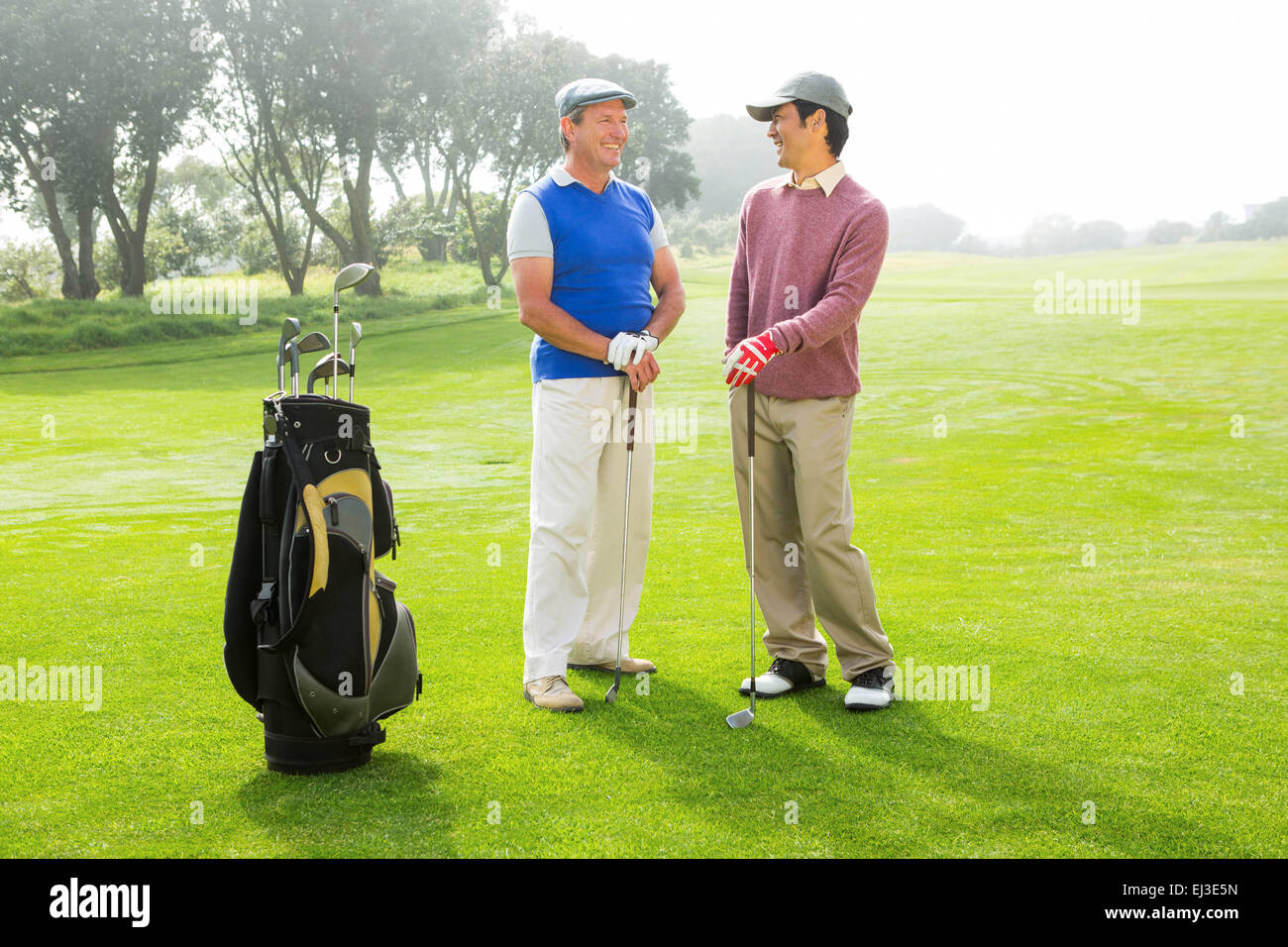 Golfing friends holding clubs - Stock Image